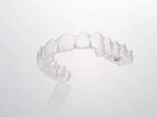 インビザラインは、1997年に米国のアライン・テクノロジー社により開発され、現在世界で140万人以上の患者様が治療を受けている新しい歯科矯正システムです。取り外し可能な透明のマウスピース(インビザライン)を用いて矯正を行います。1日20時間以上の装着と、2週間ごとの交換をご自身で行っていただき、歯を徐々に動かしていきます。その後は歯の動きを定期的に確認するために1.5〜3ヶ月ごとに通院していただくだけで大丈夫です。